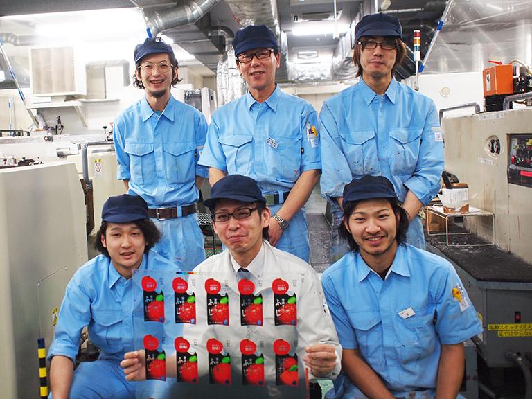 和山さん(前列中央)をはじめとした土屋工業の印刷部門スタッフのみなさん。髪の毛一本、塵ひとつで印刷に支障が出る真剣な職場の中にも、同郷の先輩、後輩なども多いそうで和気あいあいとしたチームワークの良さが伺えます。