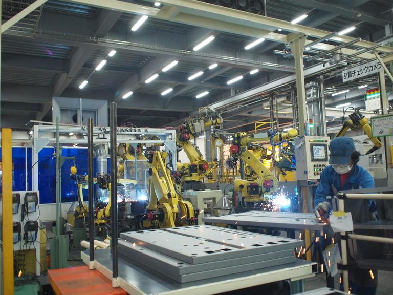 ▲溶接工程は、巨大なロボットアームと人の共同作業